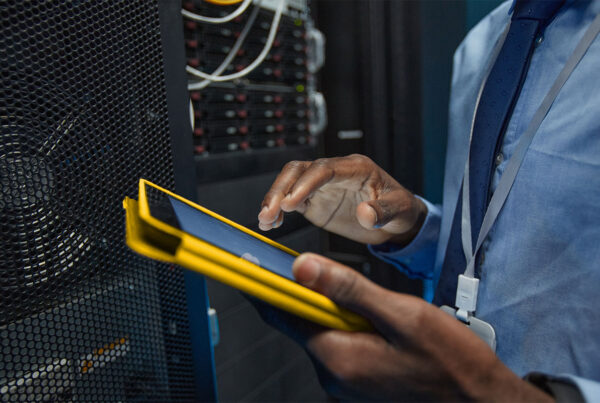 Network engineer reading tablet in a server room