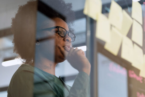 African American businesswoman looking at Post-it notes