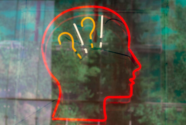 Neon sign of a human head with question marks and exclamation points.